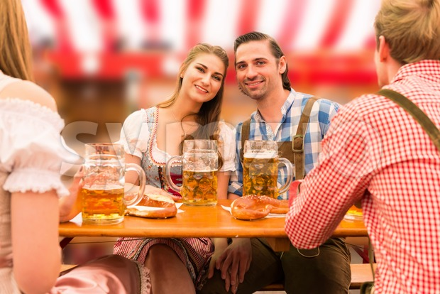 Young couple in traditional Bavarian Tracht - Dirndl and Lederhosen - in a beer tent at the Oktoberfest enjoying their ...