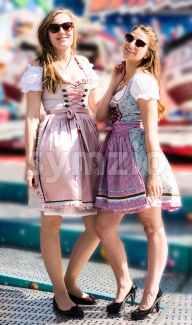 Two attractive young women at German funfair Oktoberfest with traditional dirndl dresses and joyride in the background