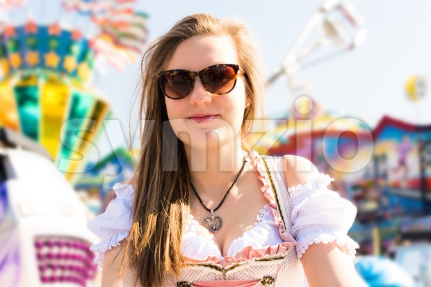 Attractive young woman at German funfair Oktoberfest wearing traditional dirndl dress and sunglasses, joyride in the background