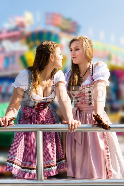 Two attractive young women having fun at German funfair Oktoberfest with traditional dirndl dresses and joyride in the background