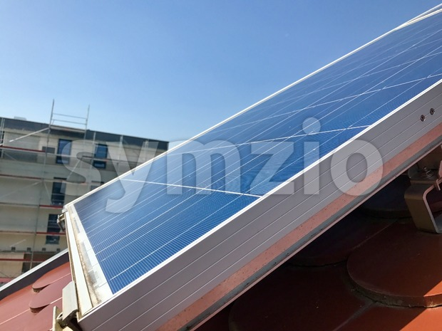 House roof with solar panels on top in a newly built area against great blue sky
