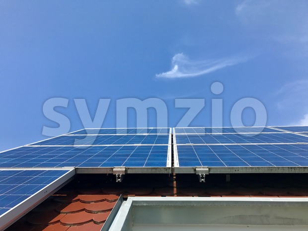 House roof with solar panels on top against great blue sky