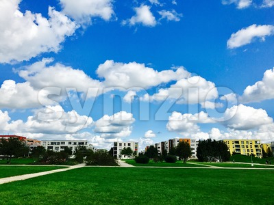 Modern apartment buildings with meadows and cloudy sky Stock Photo