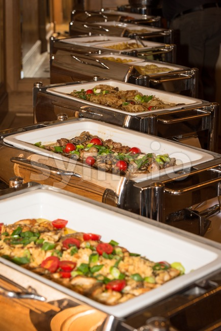 Food banquet table with chafing dish heaters on a festive event - selective focus on food in one heater