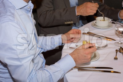 Young handsome businessman eating a soup for lunch Stock Photo