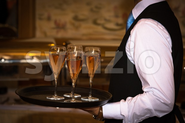 Female waiter welcomes guests with rose sparkling wine on a tray