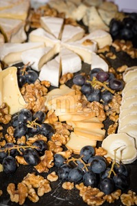 Cheese platter with different cheese, walnuts and grapes Stock Photo
