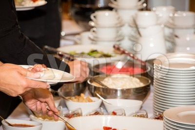 People are picking food from a buffet in a restaurant during a festive event Stock Photo