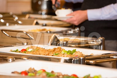 man picking food from chafing dish heaters Stock Photo