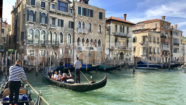 Venice, Italy - September 29,2017: Gondoliers with tourists and gondola boats on the Canale Grande in front of the famous ...
