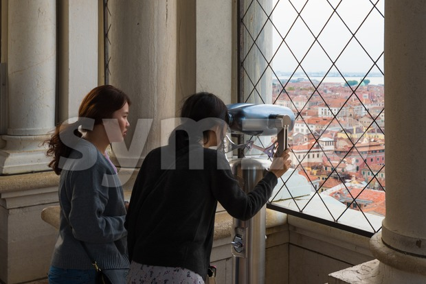 Venice, Italy - September 29, 2017: Two asian tourist girls are looking on Piazza San Marco from the bell tower ...