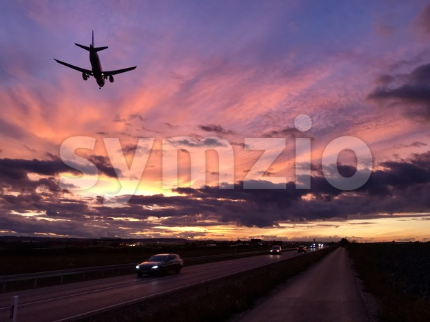 A plane is approaching Stuttgart AIrport during a dramatic sunset while crossing the highway and the main road in parallel ...