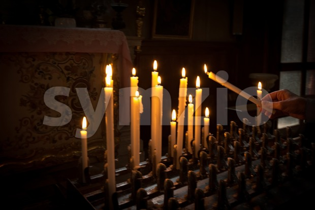 Woman lighting prayer candle aka offering, sacrificial or memorial candles lit in a church