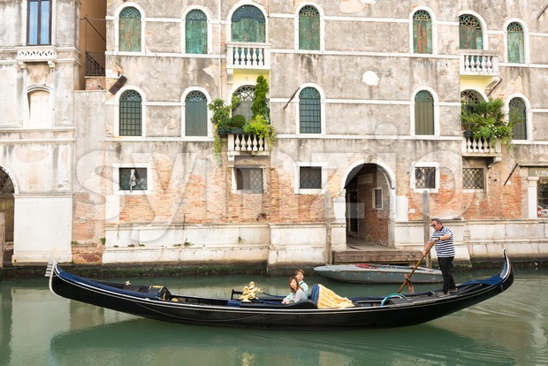 Venetian gondolier punting gondola through green canal waters of Venice, Italy Stock Photo