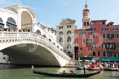 Famous Ponte di Rialto with traditional gondola passing in Venice, Italy Stock Photo