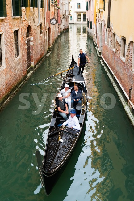 Venice, Italy - September 29, 2017: A venetian gondolier is punting a gondola through the green canal waters of Venice, ...