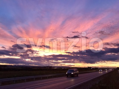 Cars driving during dramatic sunset Stock Photo