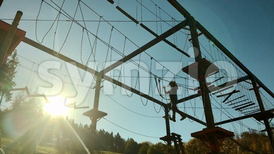 Unidentifiable boy climbing in high rope park Stock Photo