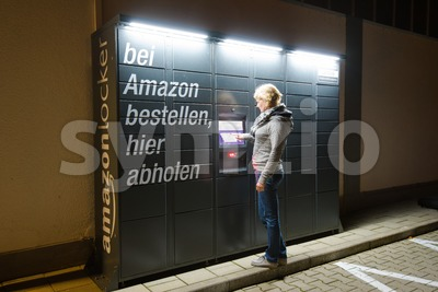 A woman is using an Amazon Locker station located next to an Aldi supermarket. Stock Photo