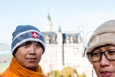 Buddhist monks in front of world-famous Neuschwanstein Castle Stock Photo