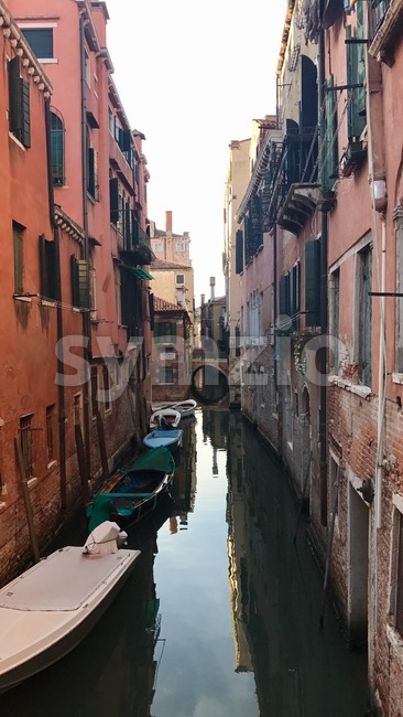 Venice, Italy - September 29,2017: Gondolier with tourists and gondola in the small canals between the famous old buildings of ...