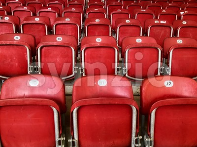 Empty red plastic seats in a stadium Stock Photo