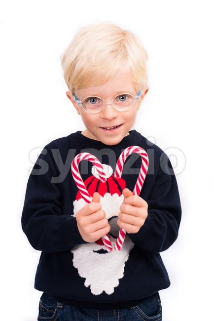 Love Christmas: A cute 4 year old boy wearing glasses and a Santa Claus pullover is holding two candy sticks, ...