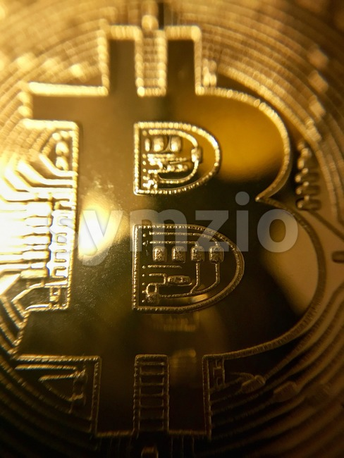 Closeup of a golden bitcoin showing the B symbol of the cryptocurrency