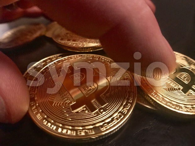 hands grabbing a golden bitcoin Stock Photo