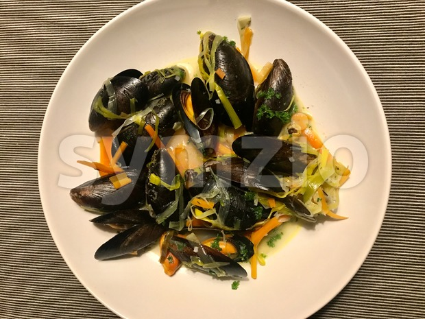 Mussels in whitewine served on a plate with parsley, carrots and leek