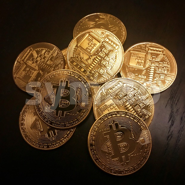 Heap of golden bitcoins, the cryptocurrency on a dark wooden table