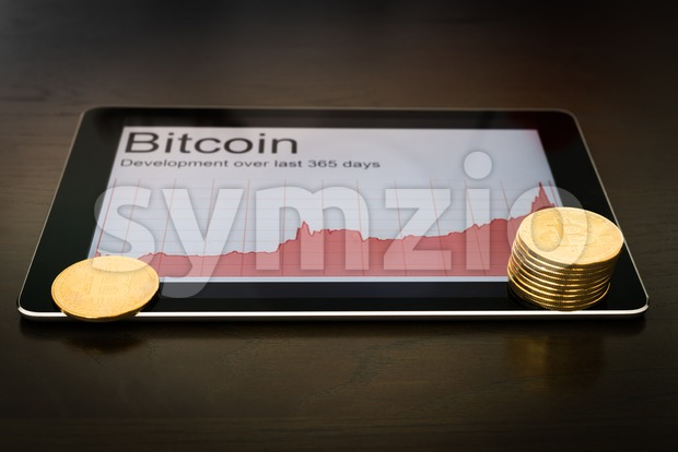 Bitcoins and rising chart on digital tablet Stock Photo
