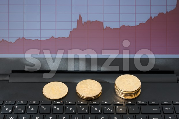 Bitcoins and rising chart on laptop computer Stock Photo