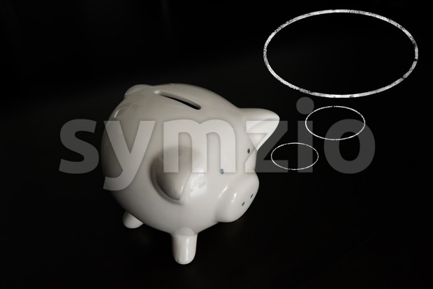 White piggy bank on dark wooden table with thought bubbles and room for your text