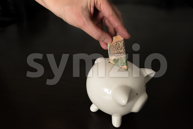 Woman putting a 500 Russian Rubles bank note into a piggy bank Stock Photo