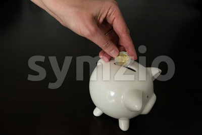 Woman putting two Euro coin into a piggy bank Stock Photo