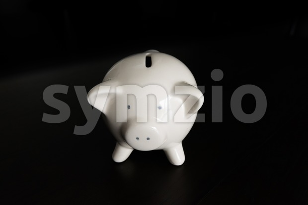 White piggy bank on dark wooden table with room for your text