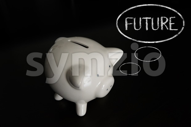 White piggy bank on dark wooden table with thought bubbles, thinking FUTURE