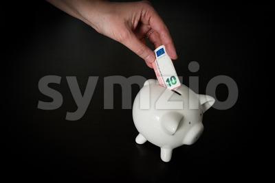 Woman putting a ten Euro bank note into a piggy bank Stock Photo