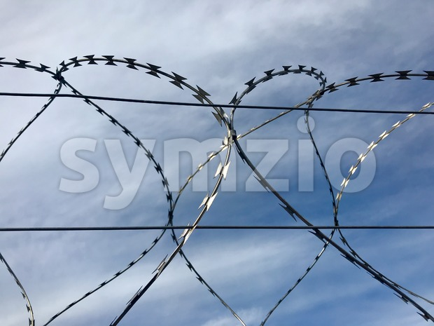 Barbed wire against great blue cloudy sky