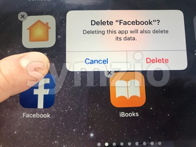 Macro image of a finger about to delete the Facebook app from an iPad screen - might be due to data privacy issues, Facebook is currently facing Stock Photo