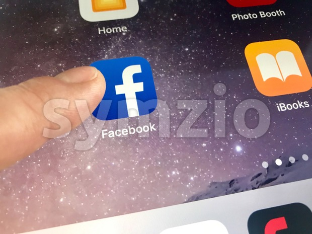 Macro image of a finger about to click the Facebook icon on an iPad screen Stock Photo