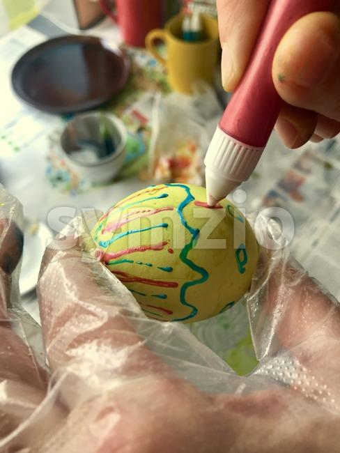 Woman painting an easter egg for holiday Stock Photo