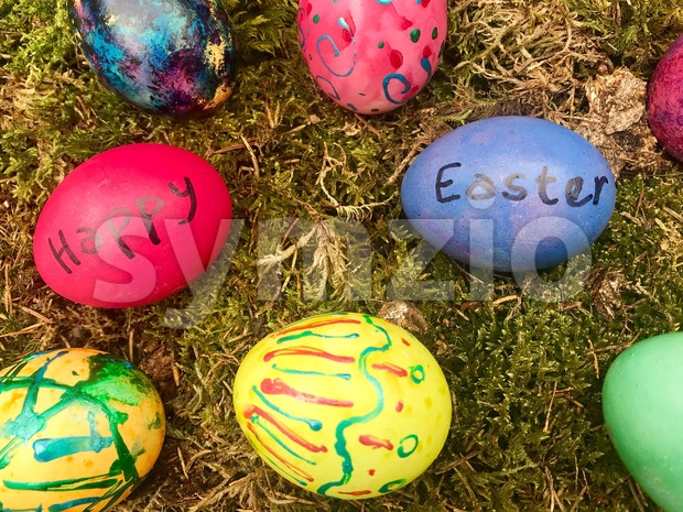 Happy Easter - Colourful Easter eggs in green moss. Stock Photo