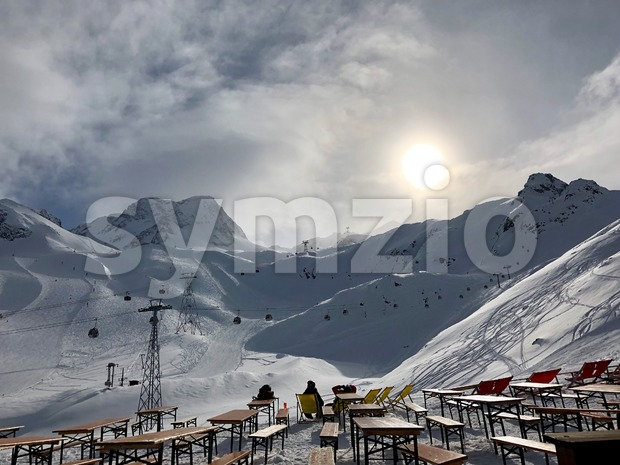 People resting in deckchairs in the Stubai glacier ski resort in Tyrol, Austria