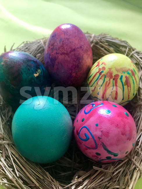 Colorful Easter Eggs in straw nest on bright background. Top view