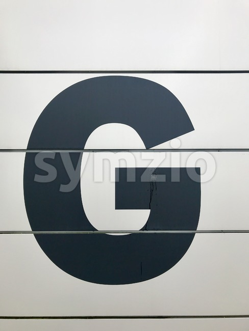 Large sign with the letter G on the entrance of a building