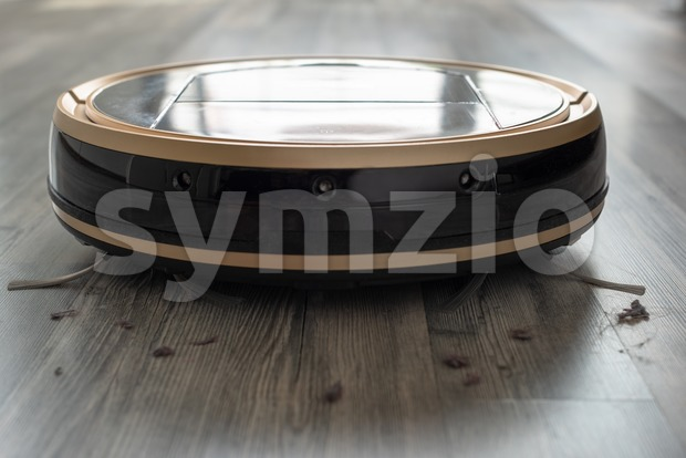 Robotic vacuum cleaner on laminate wood floor with dust around, modern and hygienic smart cleaning technology. Focus on hairs and ...