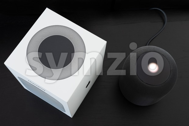 Ostfildern, Germany - June 25, 2018: Unboxing an Apple HomePod speaker: The speaker is standing next to its box, ready ...
