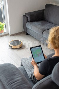 Woman is steering her vacuum cleaning robot from the sofa Stock Photo
